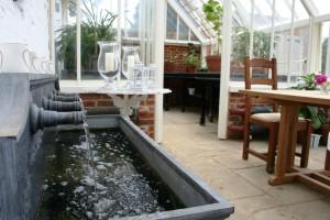 Brunnen & Sitzplatz - Lifestyle in einem Alitex Gewächshaus