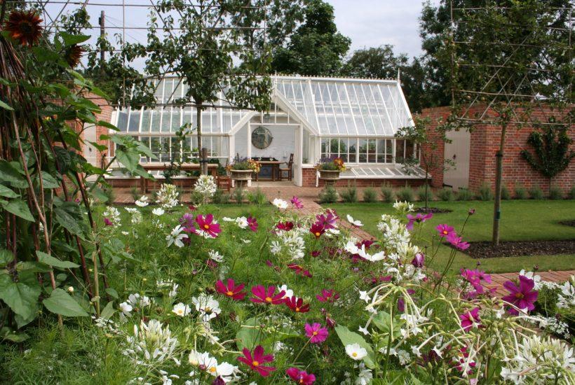 Anlehngewächshaus vor einem Blumenbeet.