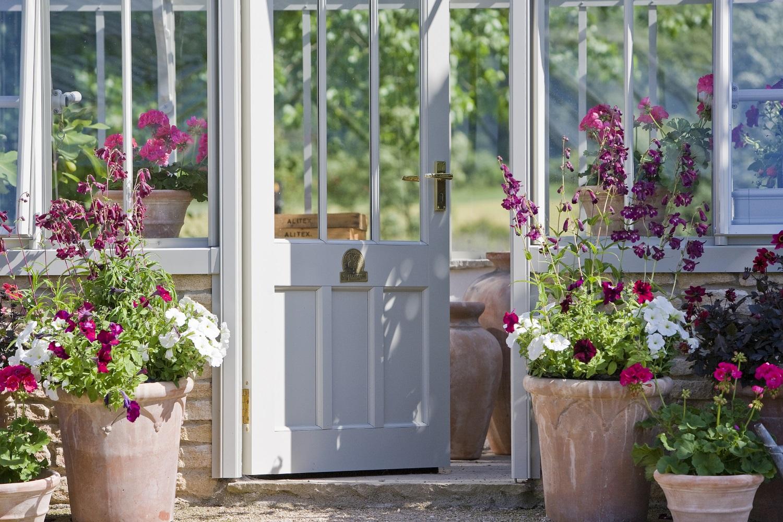 Farbenfroh bepflanzte Blumentöpfe grüßen an der Gewächshaustür.