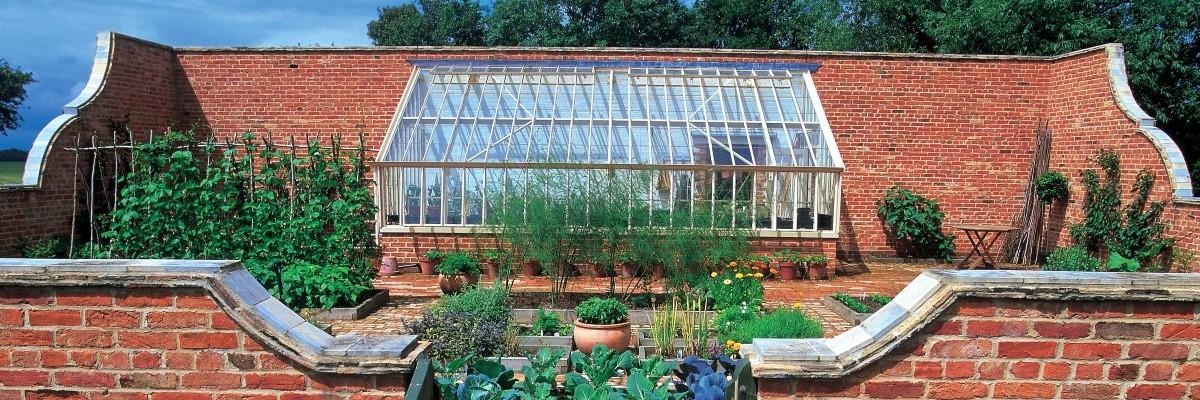 Neues Anlehngewächshaus mit Pultdach in einem Walled Garden.