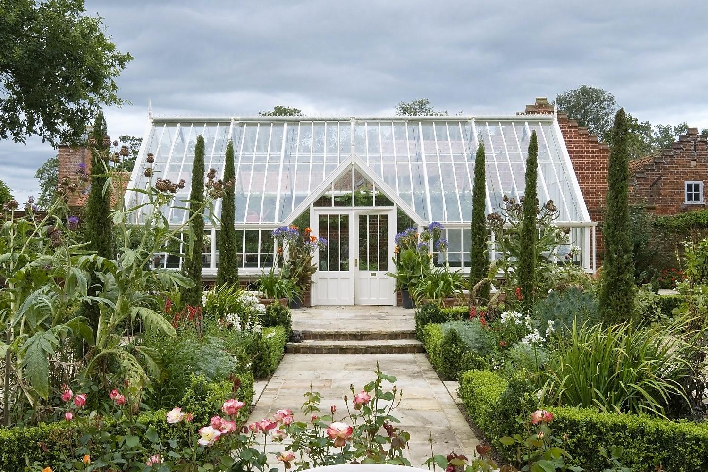 Harmonisch. Das Anlehngewächshaus mit Doppeltüren als Blickpunkt unterstreicht die Symmetrie im Gartendesign.