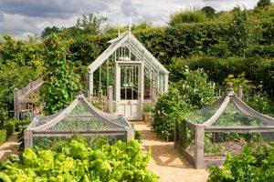 Kleines Gewächshaus in einem Gemüsegarten.