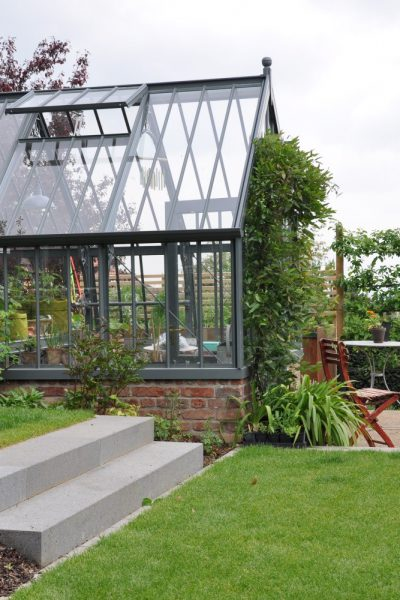 Viktorianisches Gewächshaus in einem modernen Garten.
