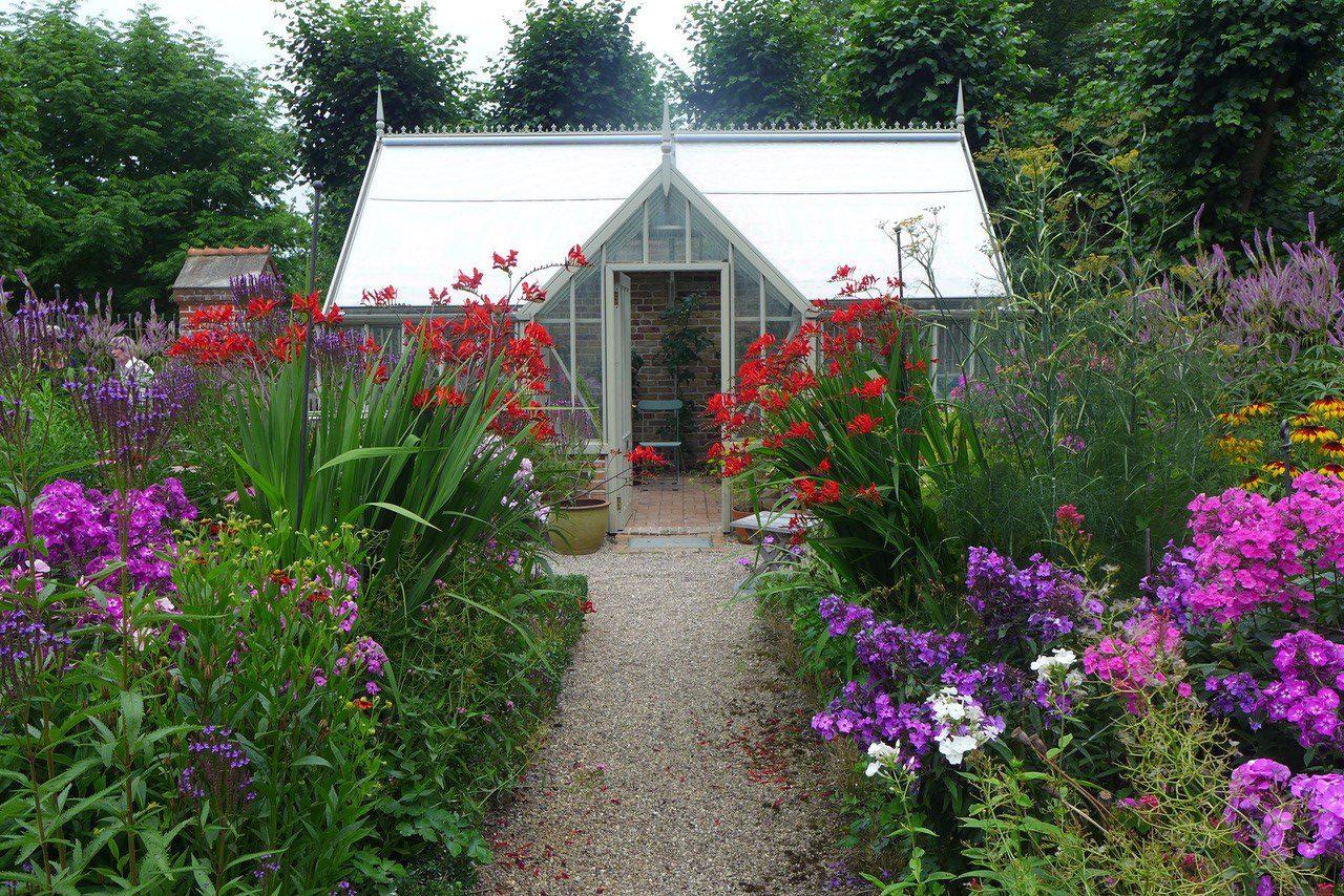 Ein Cheriton Anlehngewächshaus im Sommergarten auf der Insel Rügen.