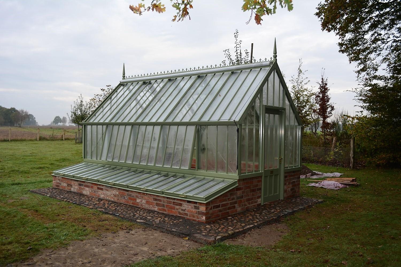 Kurz nach dem Aufbau: Ein Burton Greenhouse mit Frühbeeten im Farbton 'Sussex Emerald'.
